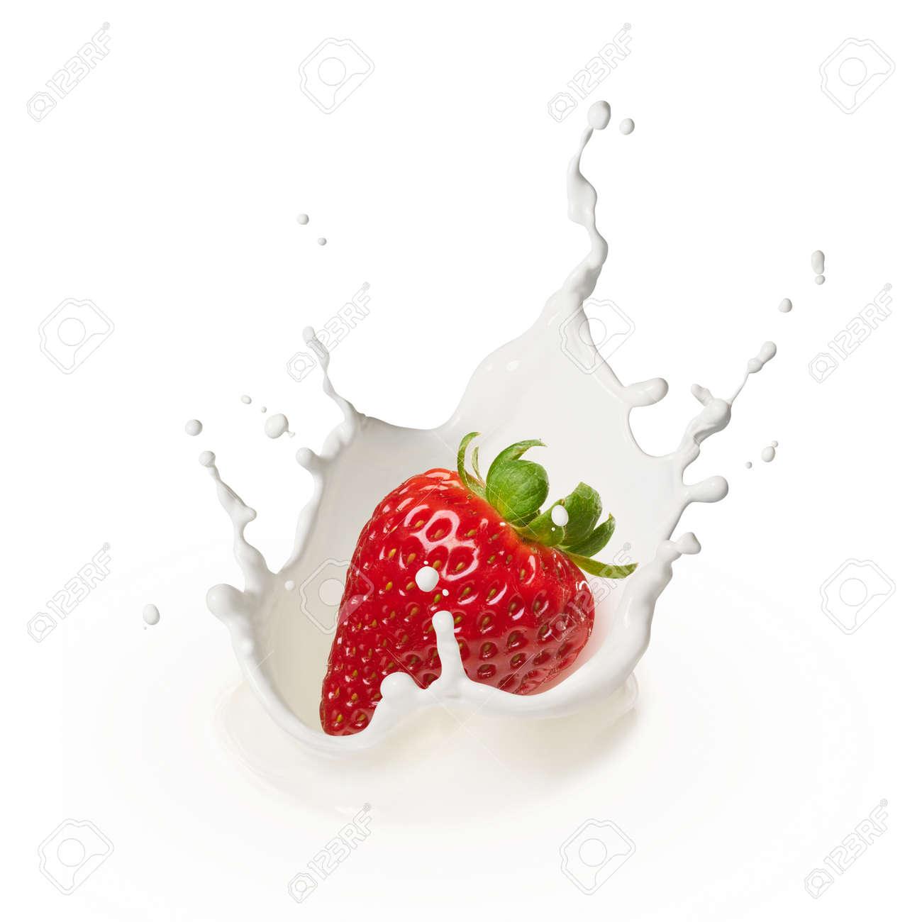 dropping a strawberry into milk causing splash - 38831324