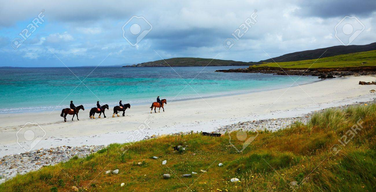 Four riders and horses on the Sellerna beach, Cleggan, in summertime, Ireland. Stock Photo - 12682019