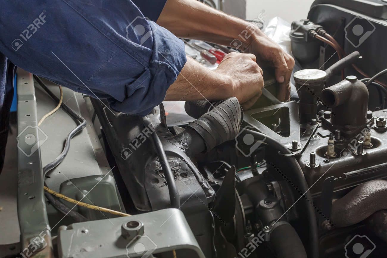 Auto Mechanic Working Under The Hood Of An Old Car Engine. Stock ...