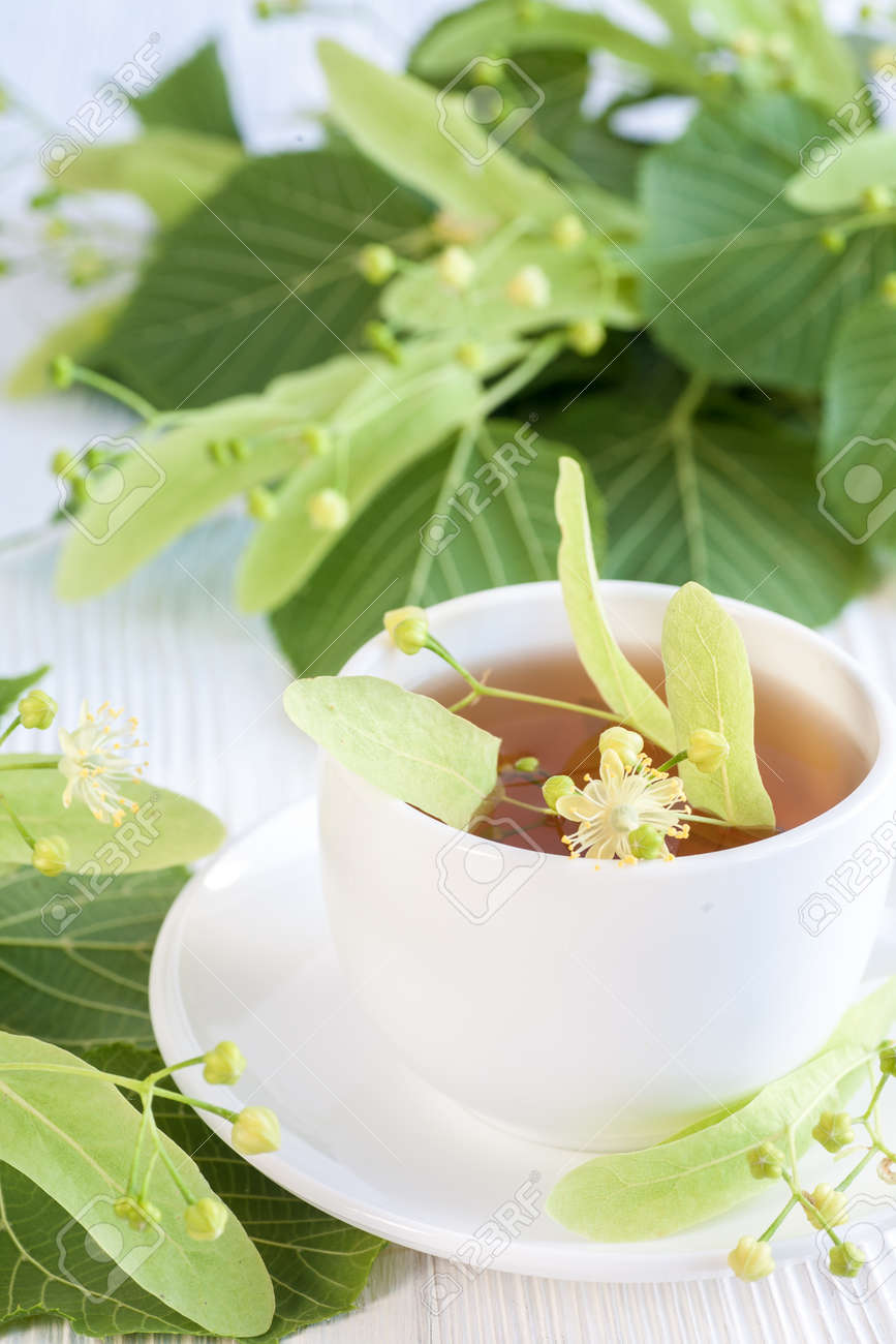 Lime flower tea in white porcelain cup with linden flower on stock lime flower tea in white porcelain cup with linden flower on wooden table stock photo mightylinksfo