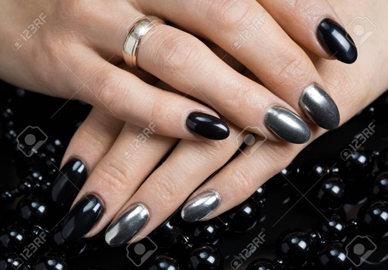 Mujeres Hermosas Manos Con Uñas De Color Negro Y Plata Con Perlas De Esmalte Negro Y Plata Sobre Un Fondo Negro