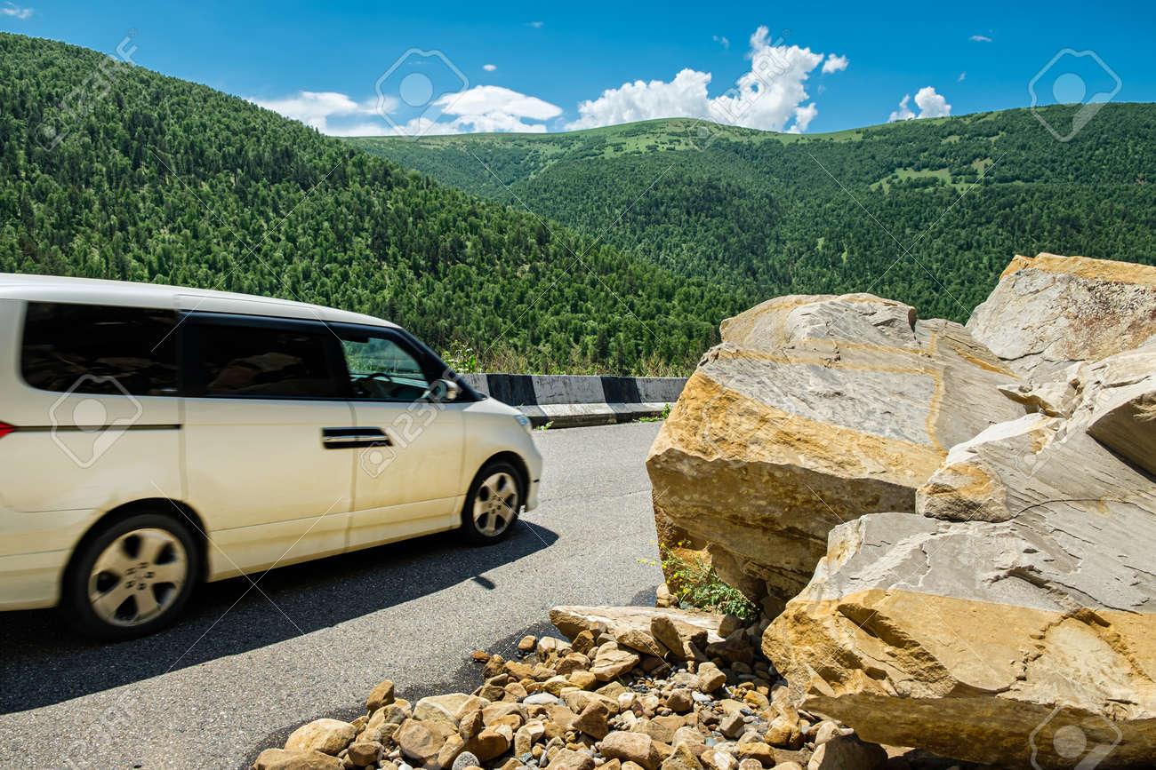 The car drives around the rockfall partially blocked the mountain road. - 141669746