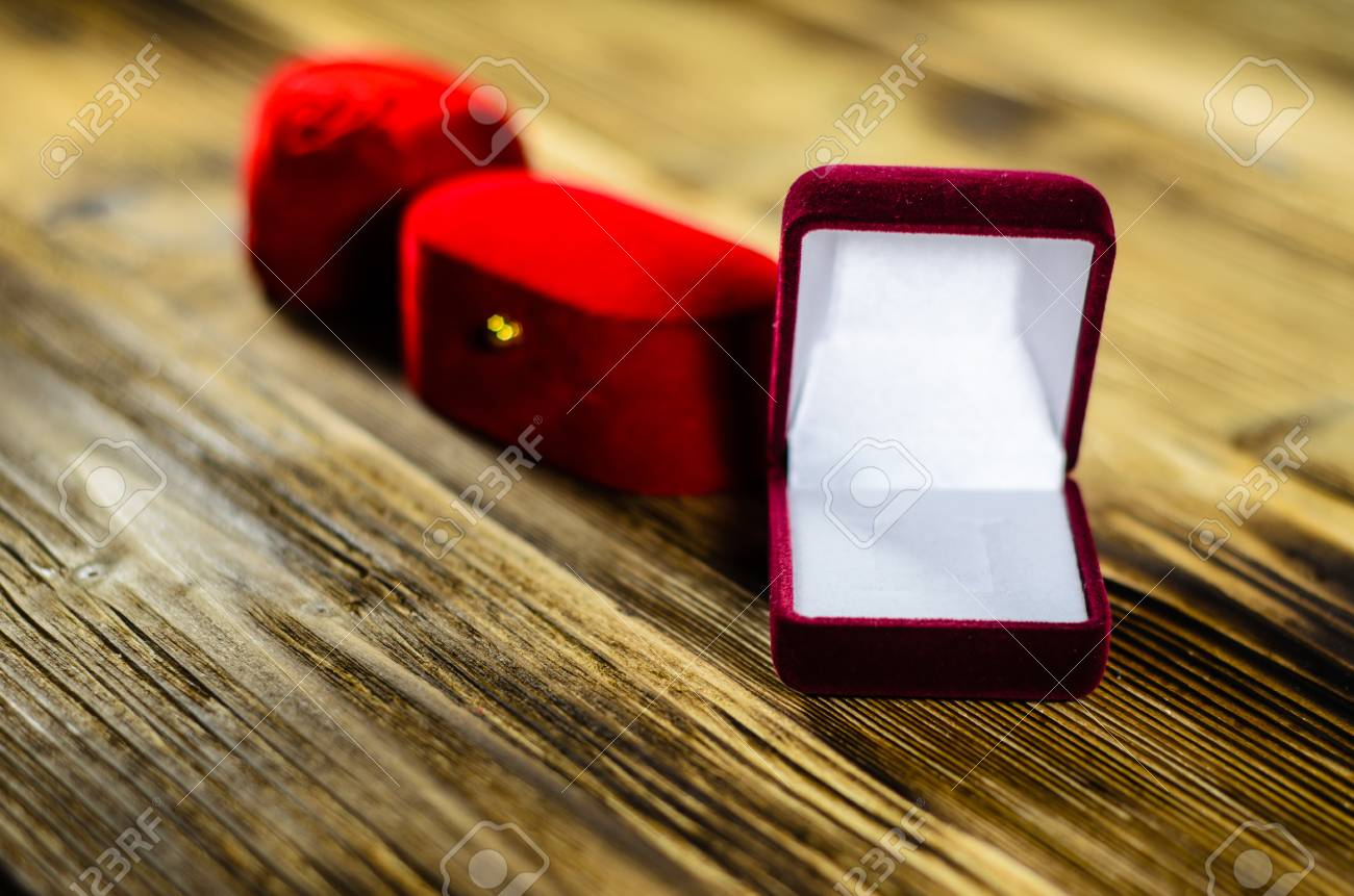 Different Red Velvet Jewelry Boxes On Wooden Table Stock Photo
