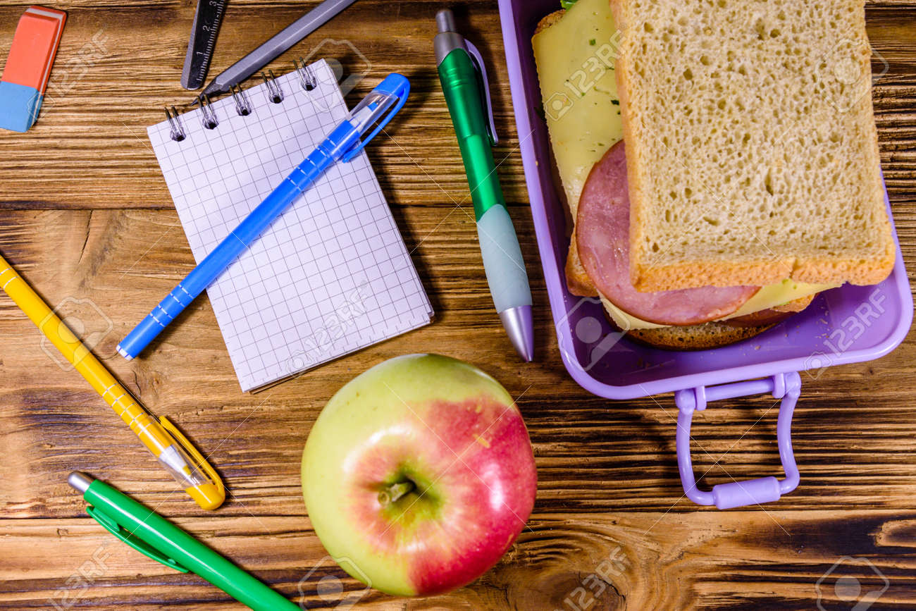 Ripe apple, different stationeries and lunch box with sandwiches on wooden table. Top view - 150620794