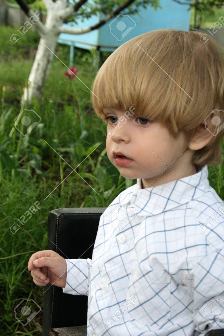 Caucasian Blue Eye And Blonde Hair Boy In The Garden Stock Photo