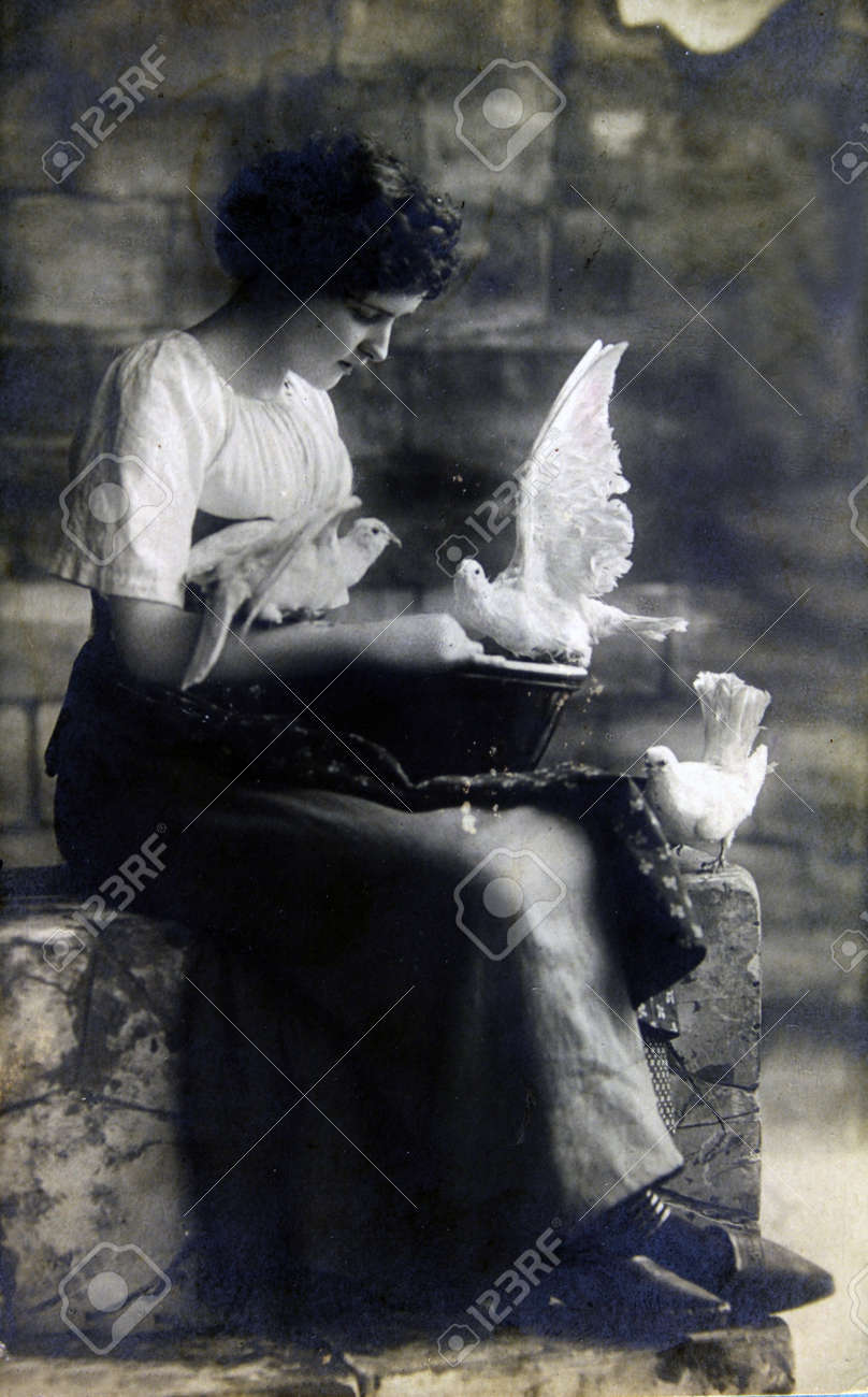GERMANY - CIRCA 19100: Postcard printed in the Germany shows Woman sitting on stone steps, feeding white doves, circa 1910 Stock Photo - 11654125