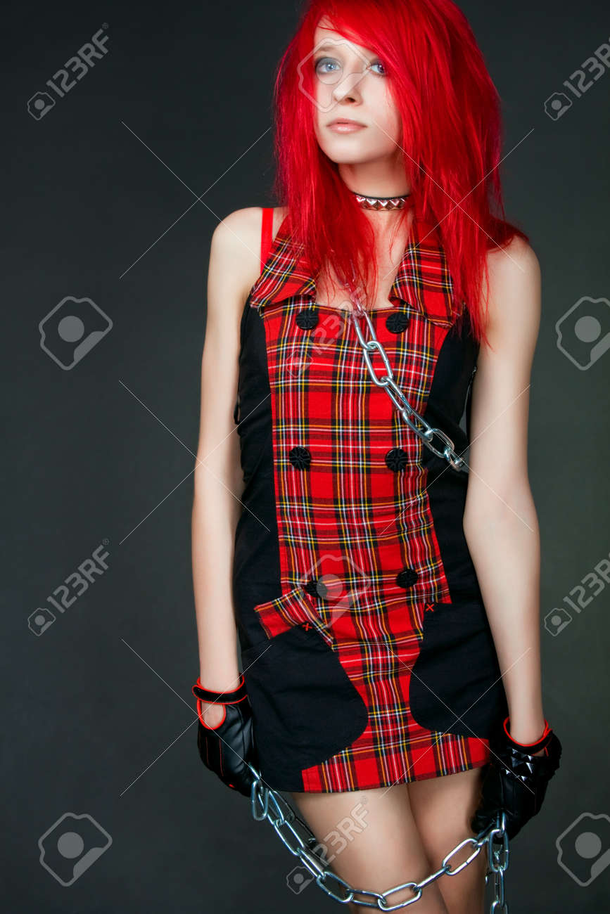 Redhead girl in red dress bounded by chains posing over gray Stock Photo - 12163226