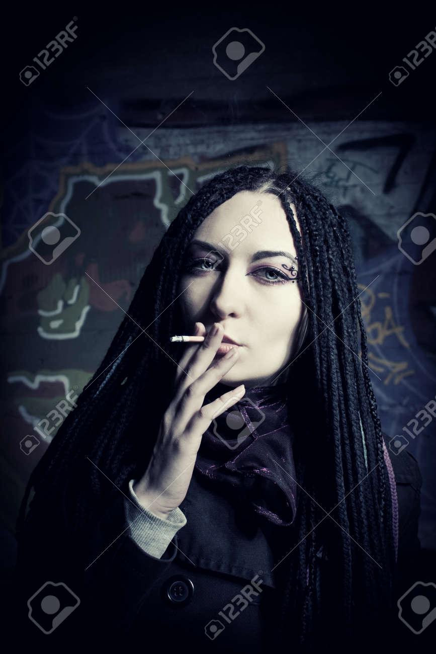 Pretty cute darkhaired pale girl smoking over graffiti Stock Photo - 12162052