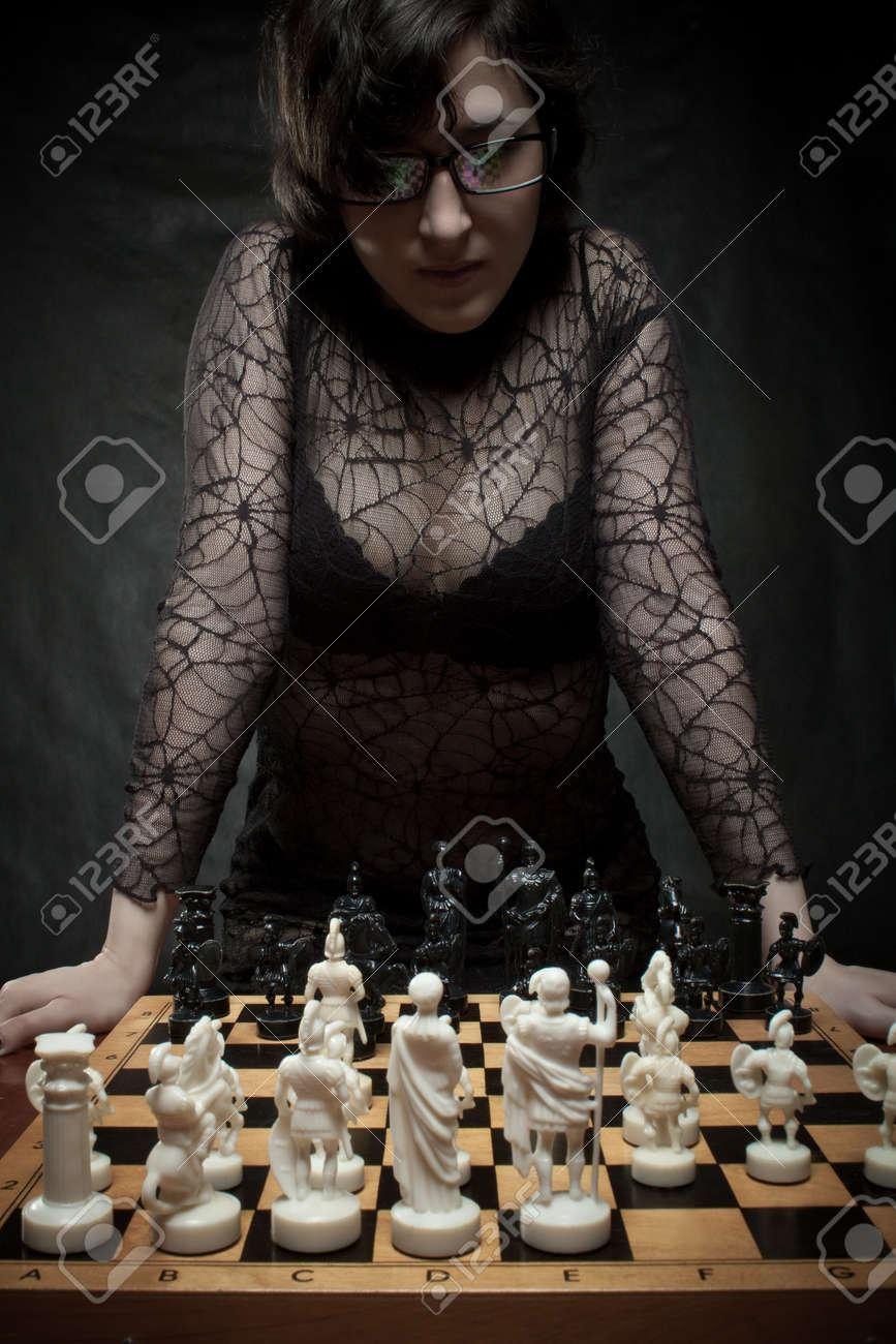 Pretty girl plyaing chess over dark Stock Photo - 12163538