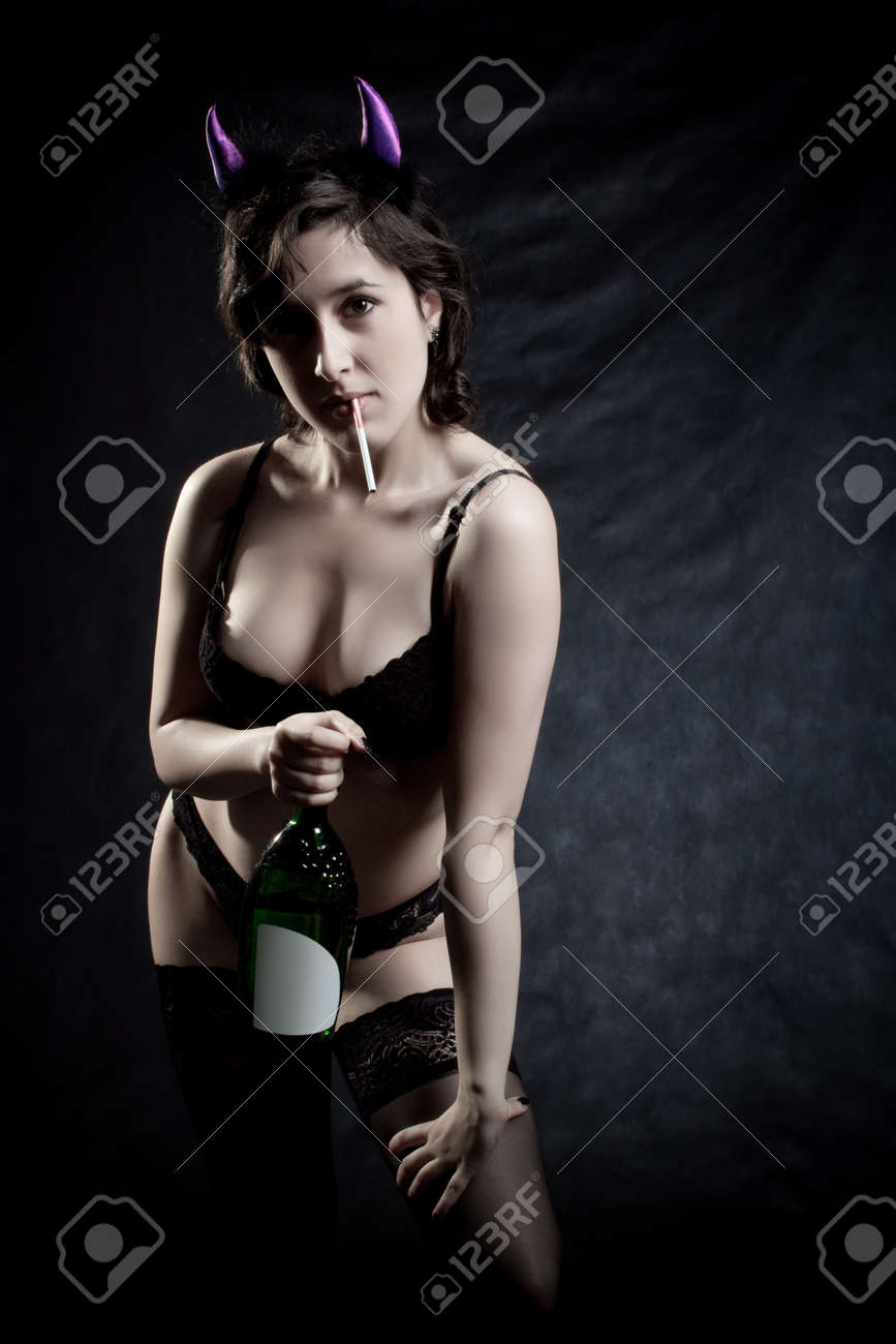 Pretty girl posing with bottle of wine over dark background Stock Photo - 12161805