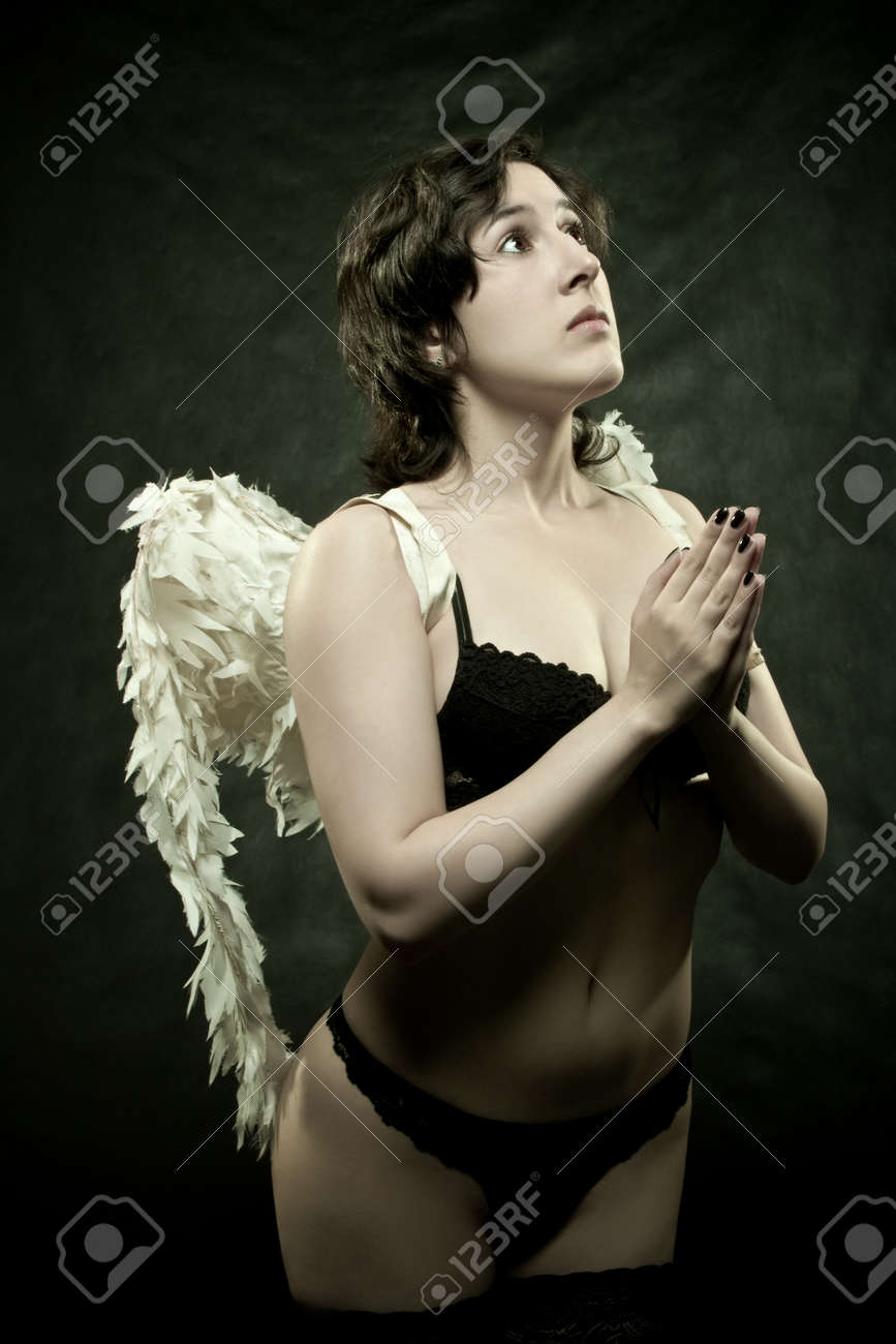 pretty sexu angel praying over dark background Stock Photo - 12162062