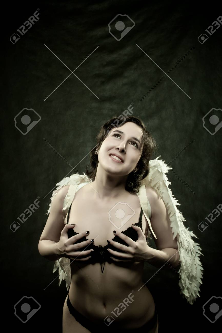 pretty sexy angel posing over dark background Stock Photo - 12162921