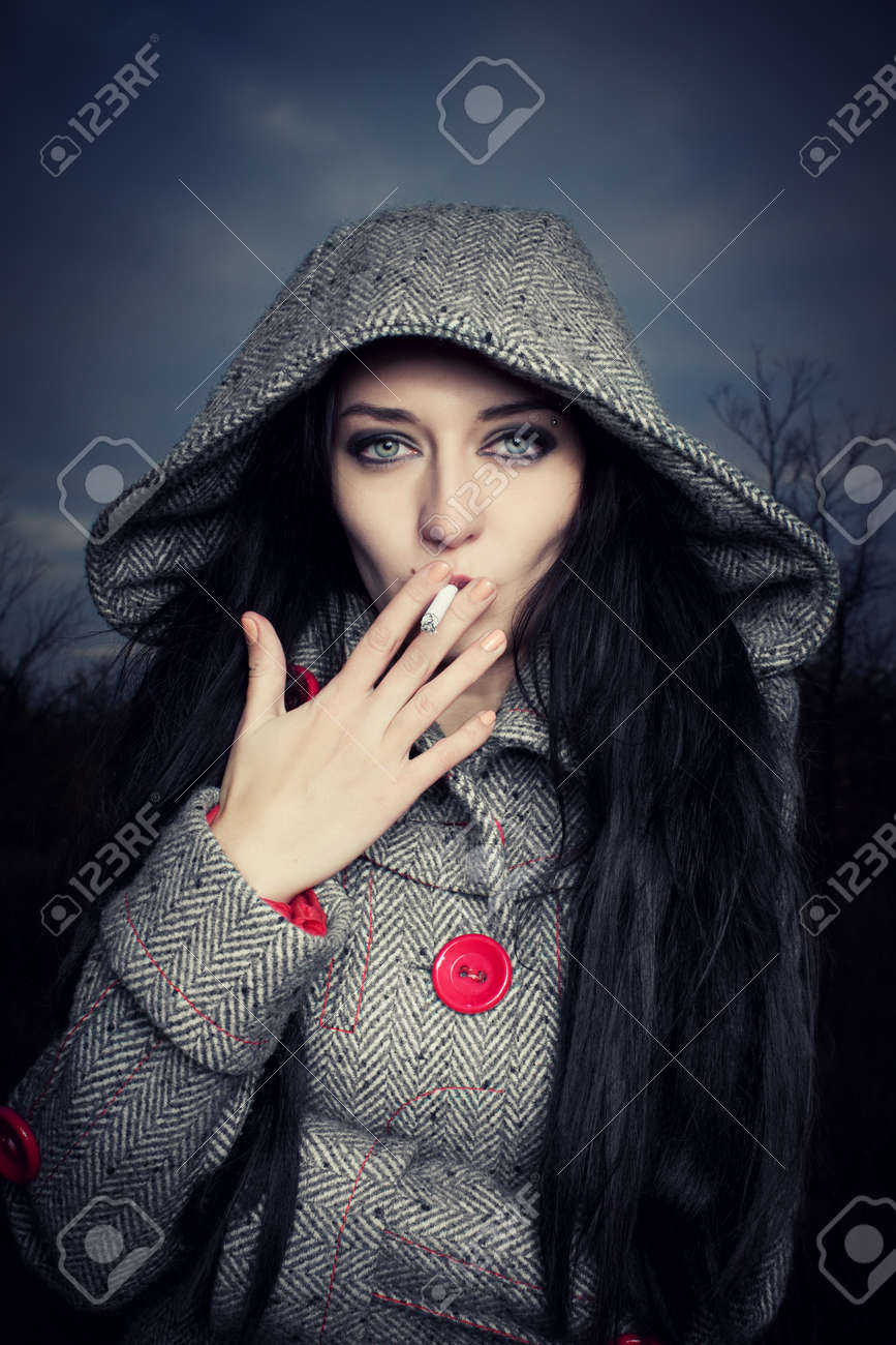 Smoking pretty dark-haired girl standing over cloudy octrober sky Stock Photo - 12386704