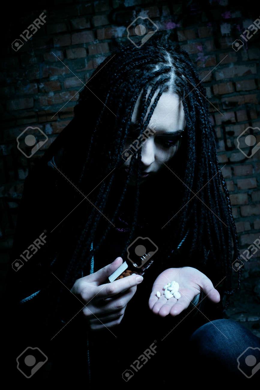 sad girl posing in the dark room with pills Stock Photo - 12386711