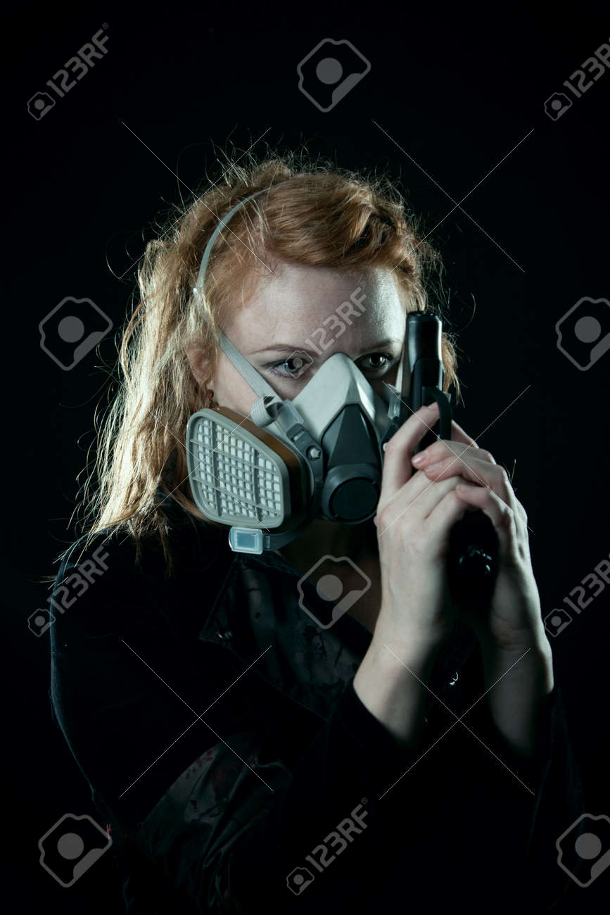 Redhead girl with pistol in respirator posing over black background Stock Photo - 12861975