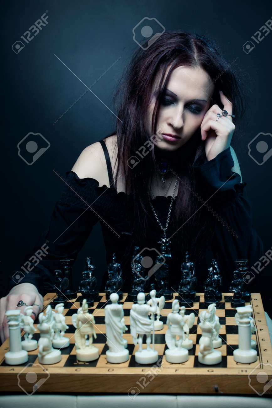 Pretty gothic girl playing chess over dark background Stock Photo - 13228098