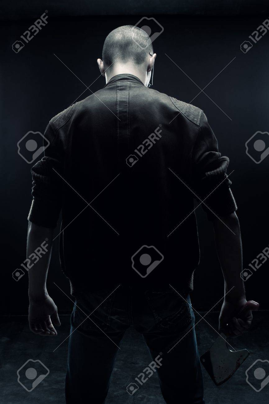 Horrible maniac with bloody chopper posing over dark background Stock Photo - 13536992