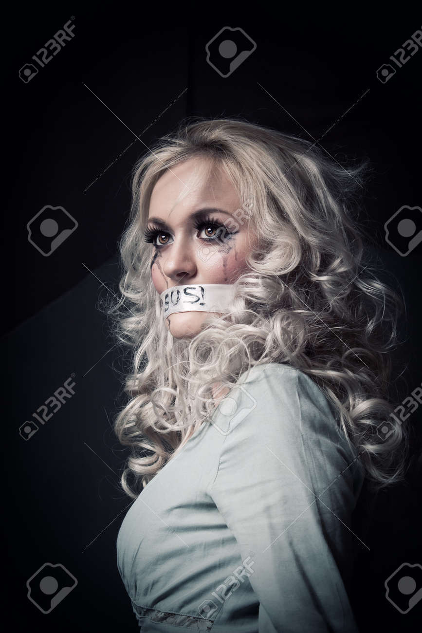 Pretty young girl with sealed mouth posing over dark background Stock Photo - 14381781