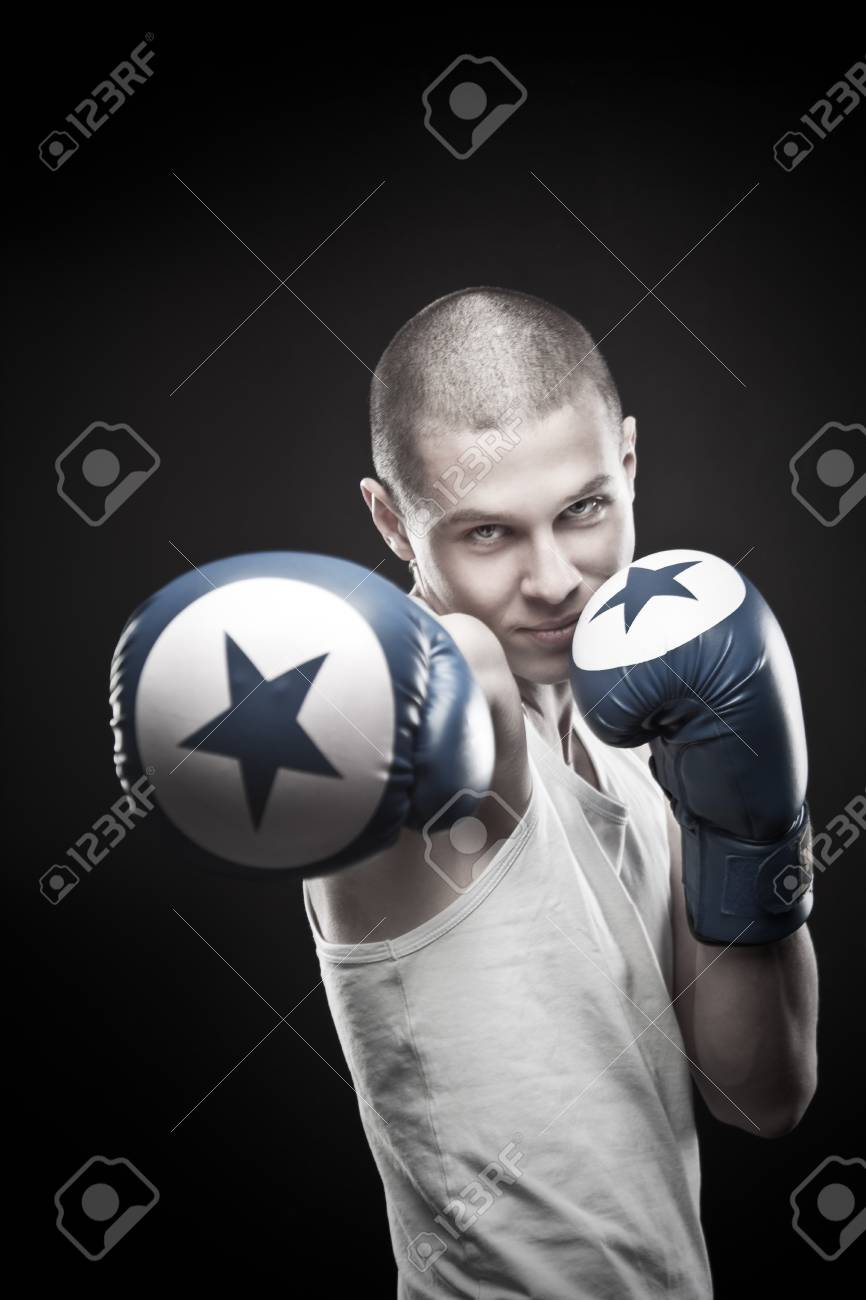 Young aggressive boxer posing over dark background Stock Photo - 17383339