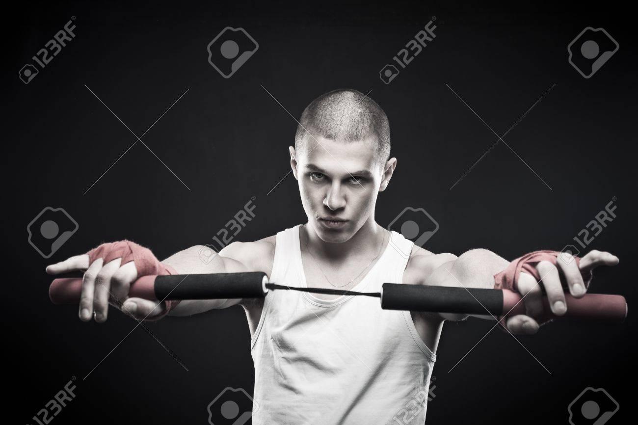 Young man posing with  nunchaku over dark background Stock Photo - 17383345