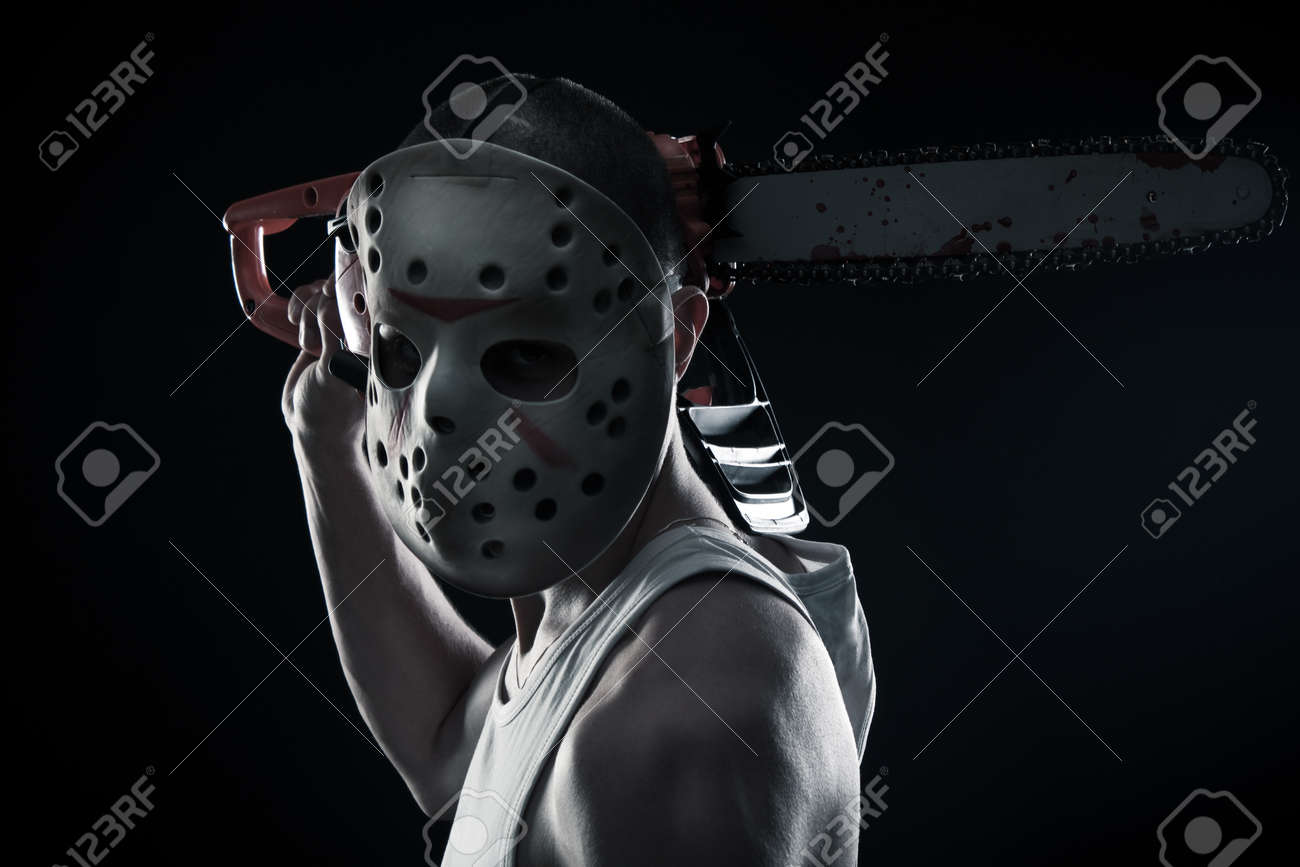Horrible maniac with bloody chainsaw posing over dark background Stock Photo - 17450503