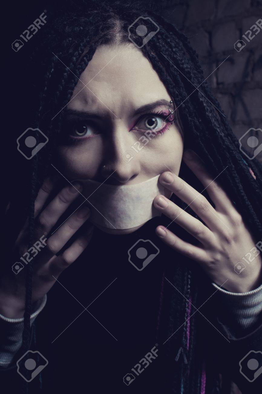 Young pretty scared girl with sealed mouth over wall Stock Photo - 17848990