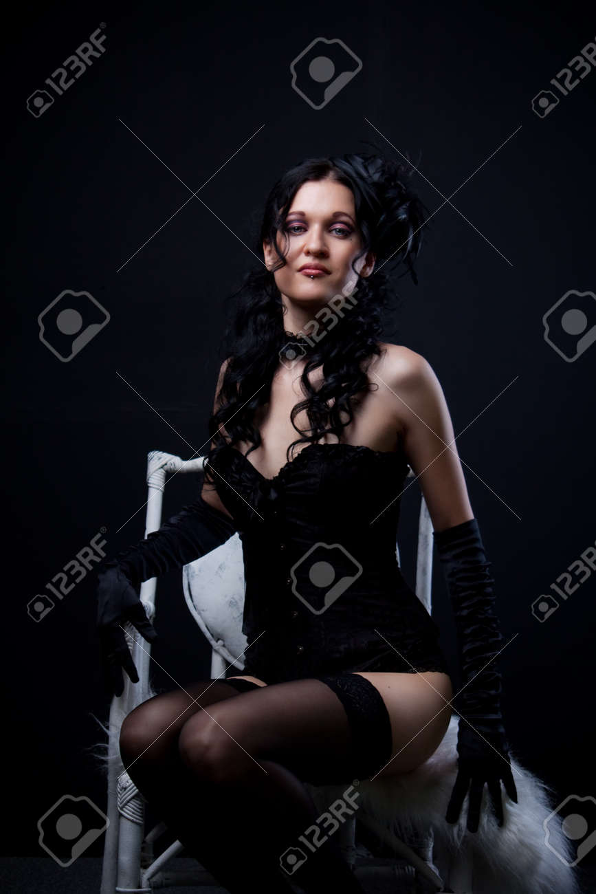 Seductive old-fashioned girl in black sits on white chair Stock Photo - 19803381