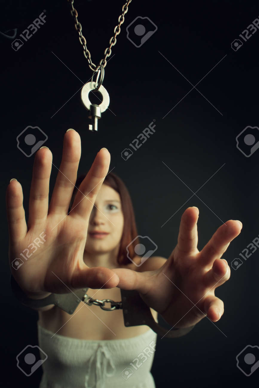 Frustrated bounded cute girl trying to grab the key over black Stock Photo - 20047778