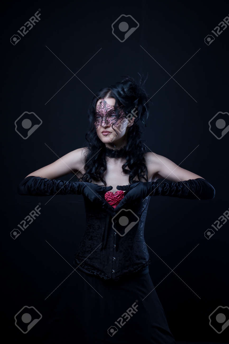 Pretty old-fashioned lady in mask with heart over dark background Stock Photo - 20443309