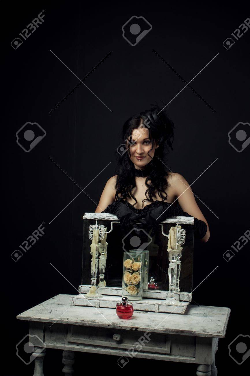 Portrait of pretty old-fashioned  actress standing behind mirror with candles Stock Photo - 20443311