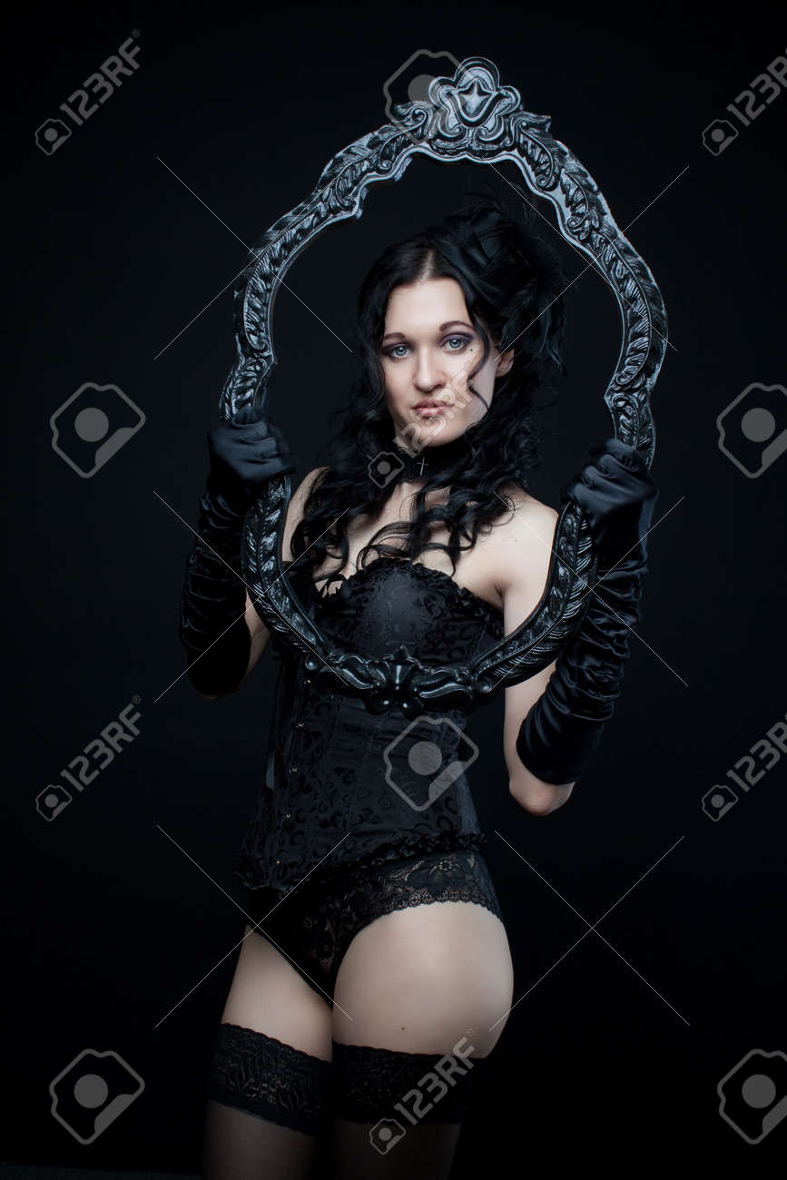 Attractive gothic girl in black corset and panties with frame over dark background Stock Photo - 20961717