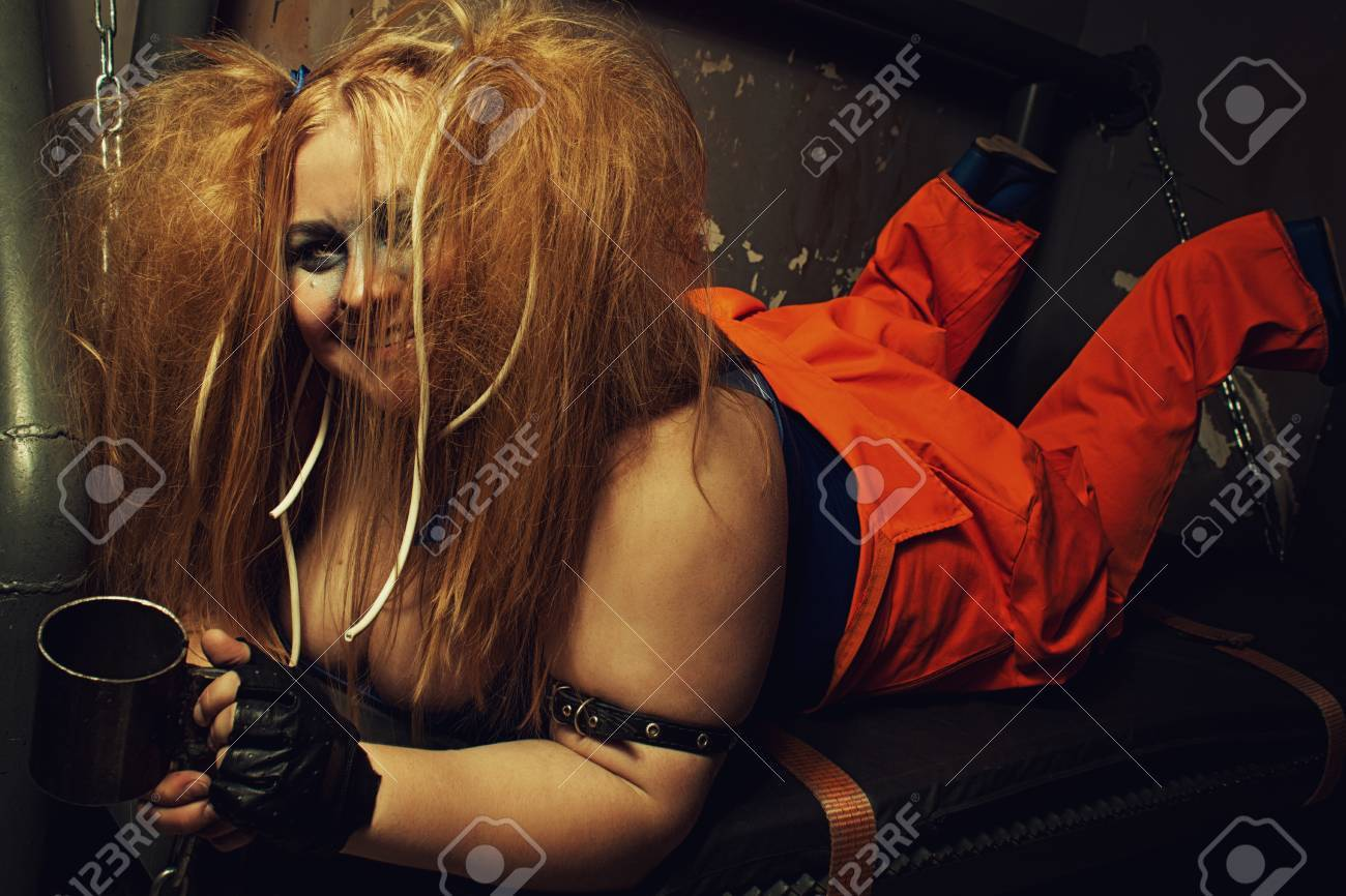 Funny prisoner in orange clothes laying on a bed in her cell Stock Photo -  40760101