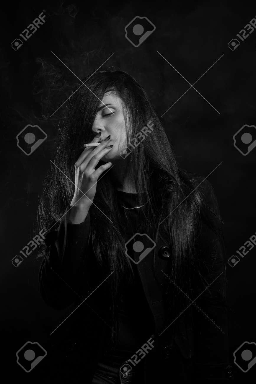 Pretty sad girl smoking over dark background stock photo 89762440