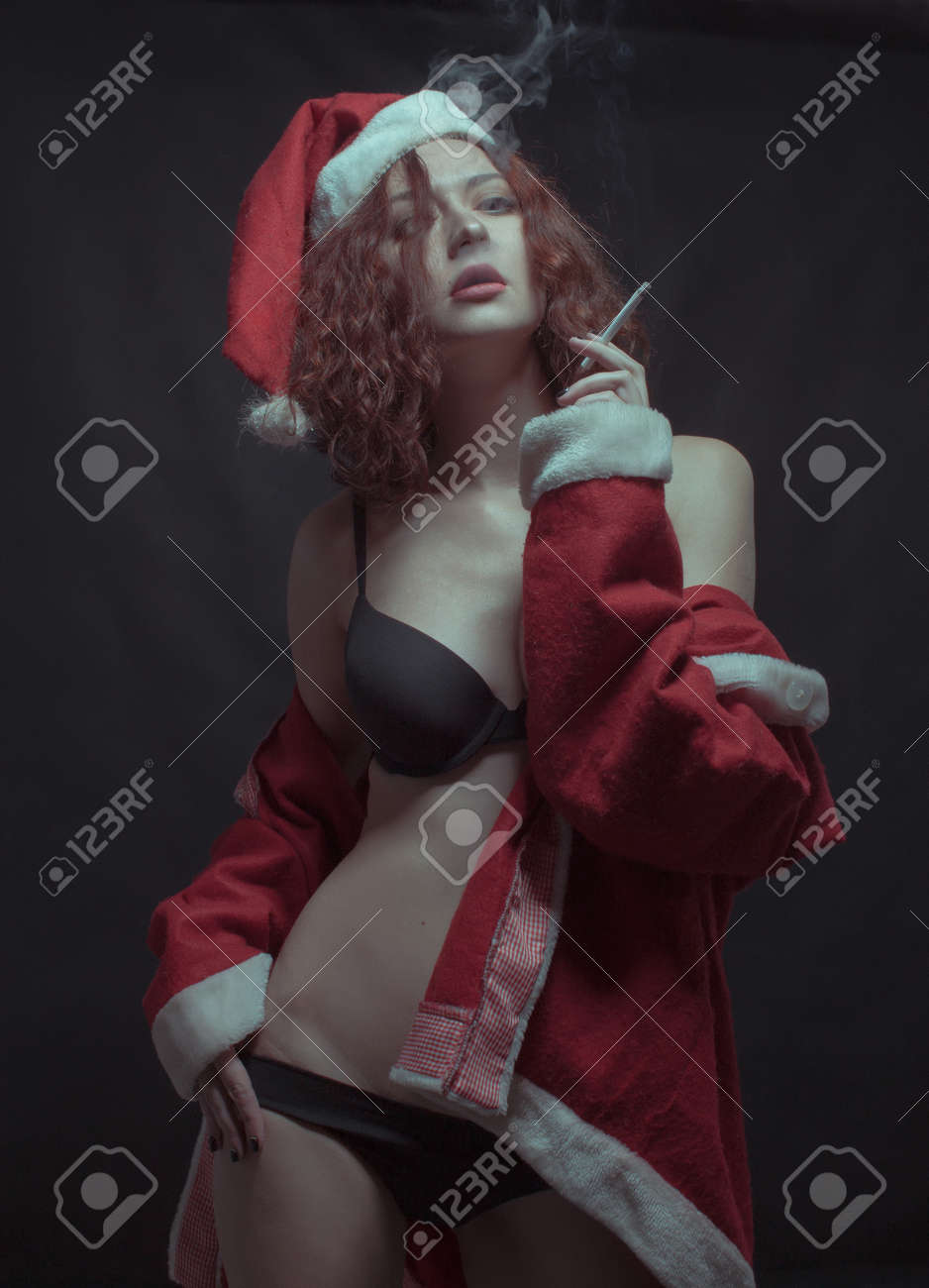 Seductive girl in Santa's costume smoking over dark background - 120790704