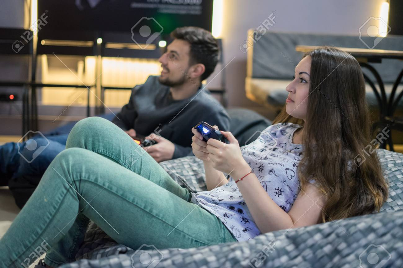 Happy Couple Friends Playing Video Games With Joystick Sitting