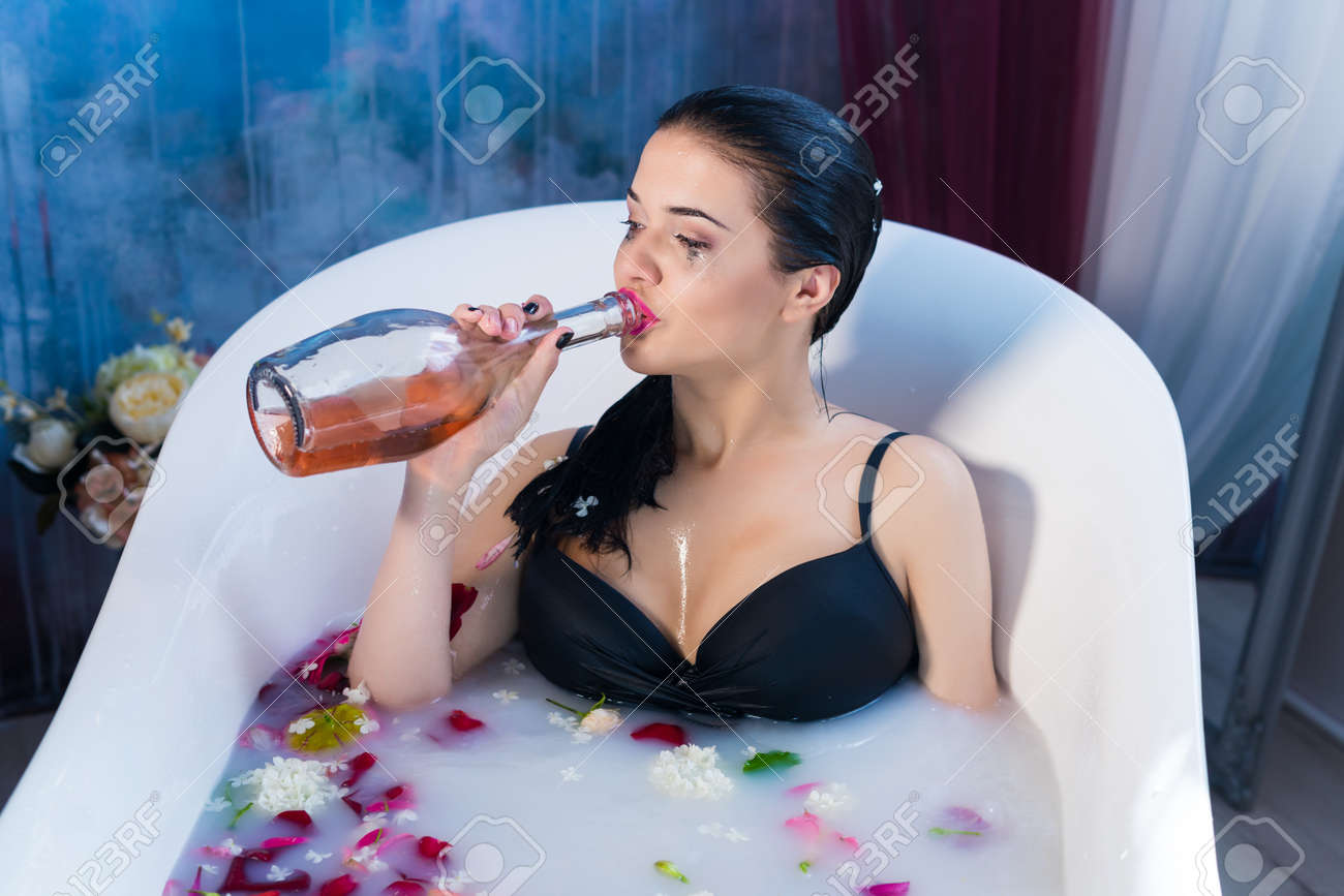sexy brunette drunk woman relaxing in a hot bath stock photo