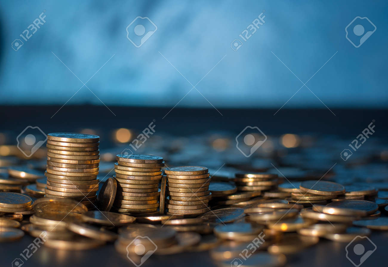 Banking and money trading. Golden metal coins stacked in different combinations on dark blue blurred background. Serbian metal coin, copy space - 129756236