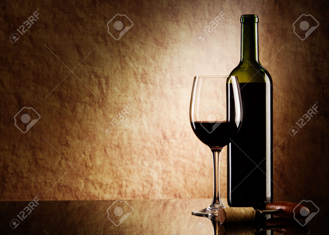 green bottle with red wine and glass and cork with a corkscrew on a old stone Stock Photo - 10060039
