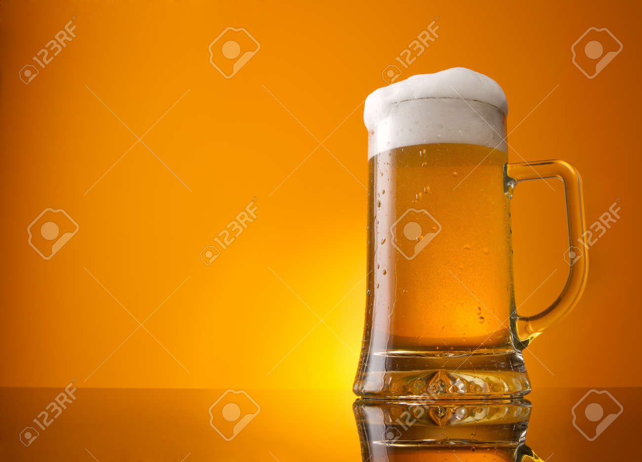 Glass of beer close-up with froth over orange background - 10693387