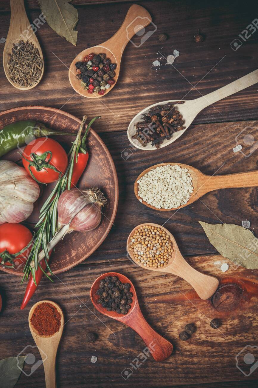 Different spices in wooden spoons and different ingredients for cooking, cherry tomatoes, garlic, coriander and red pepper - 139191337