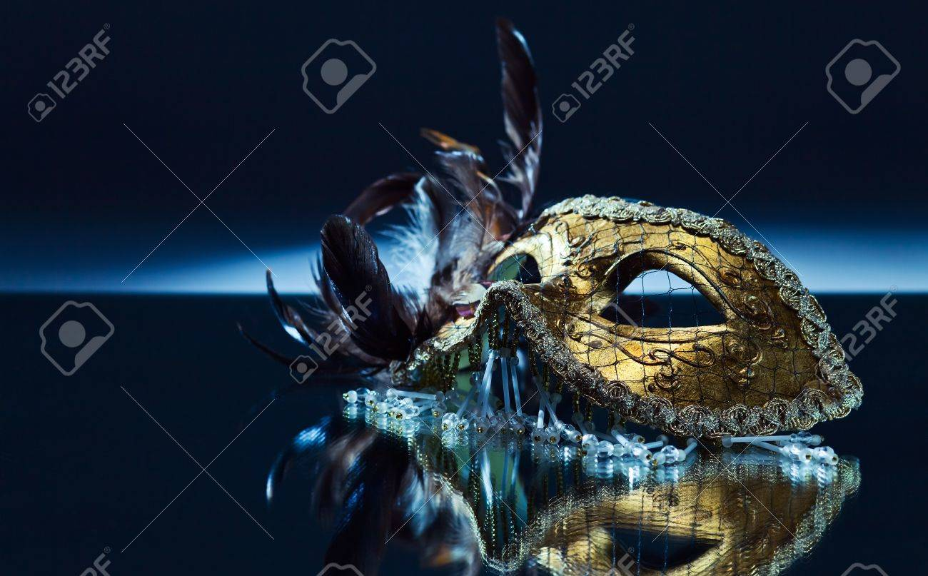 The Venetian mask with feather on a mirror table - 15742115