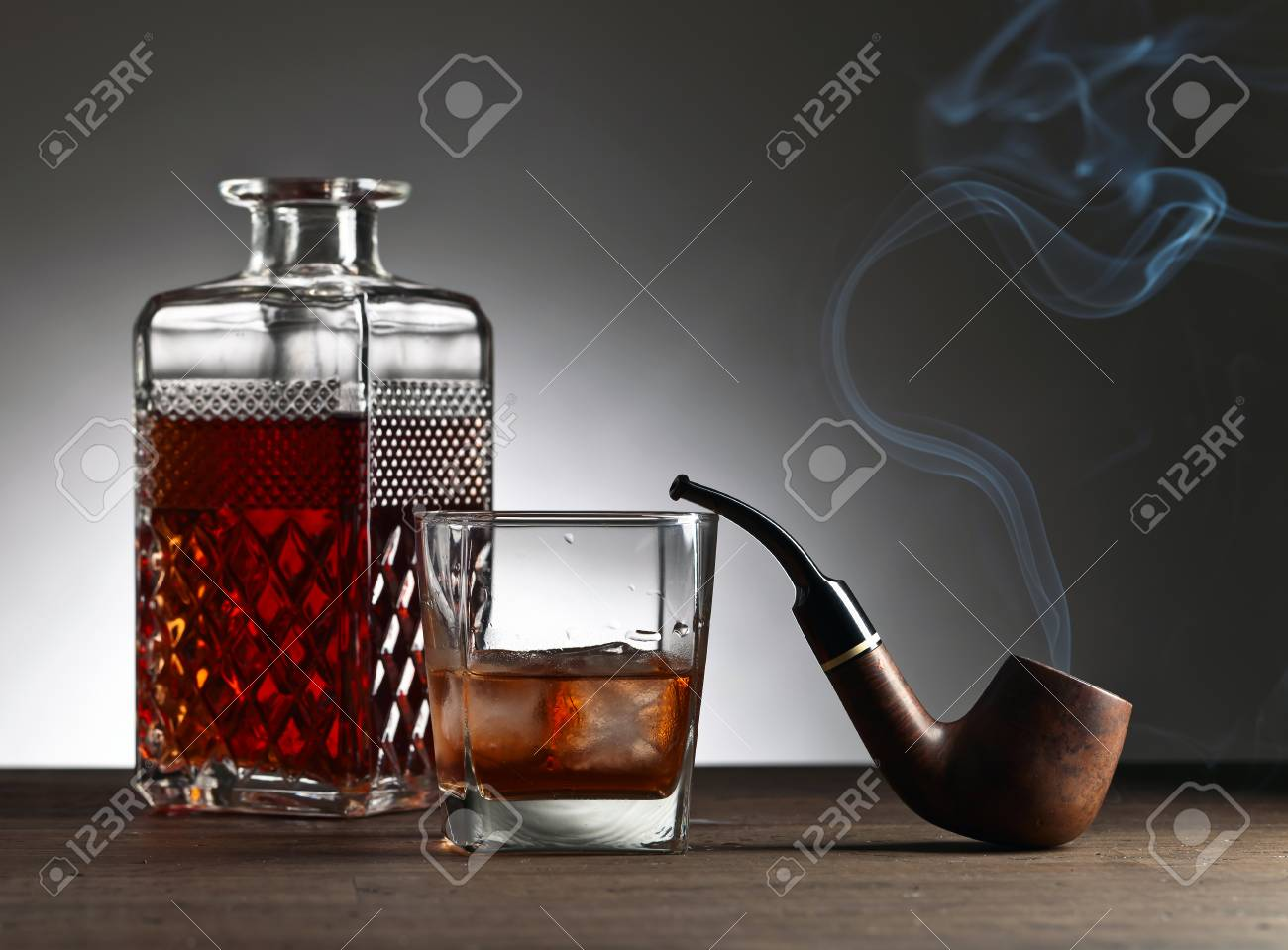 Glass of whiskey and pipe on a old wooden table