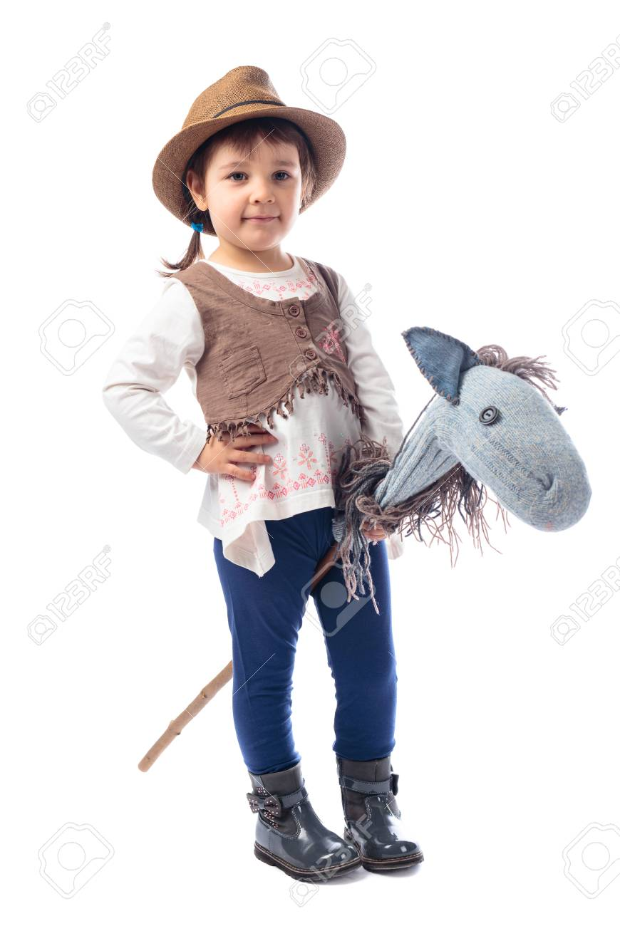 Cute little girl dressed like a cowboy playing with a homemade horse. Isolated on a white background. Expressive facial expressions. - 98117370