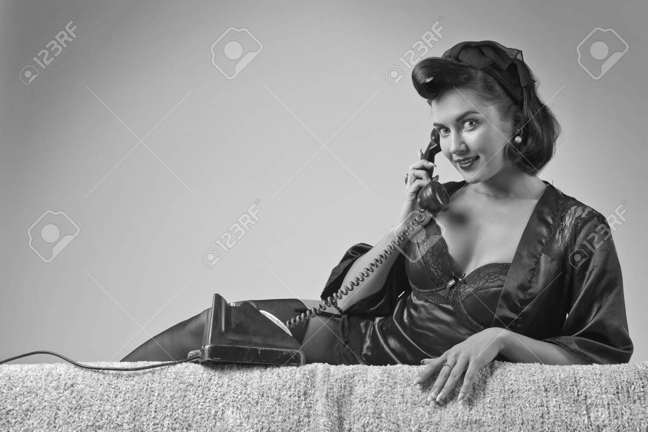 Black and white beautiful brunette woman in pin up style speaking via vintage phone attractive young woman in