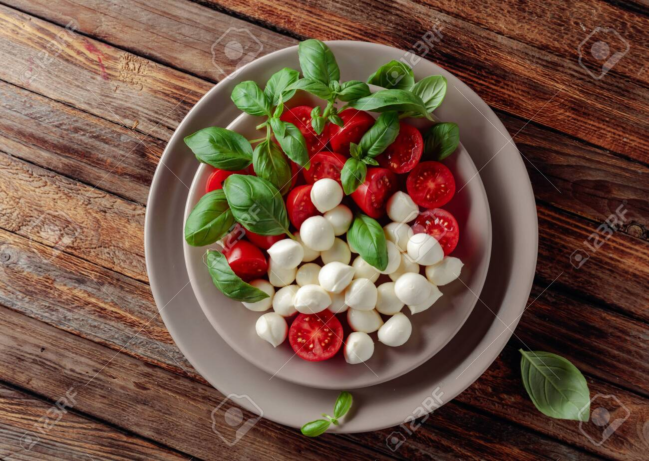 Caprese salad with tomato, mini mozzarella and basil on a old wooden table. Italian food and healthy vegetarian diet. - 149415211