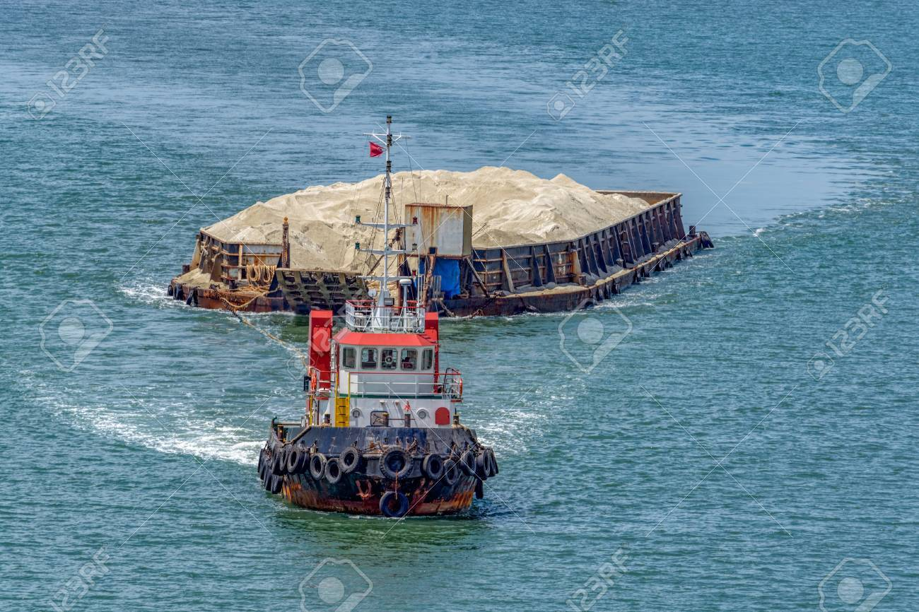 The tug boat towing a barge with sand in coastal waterway near