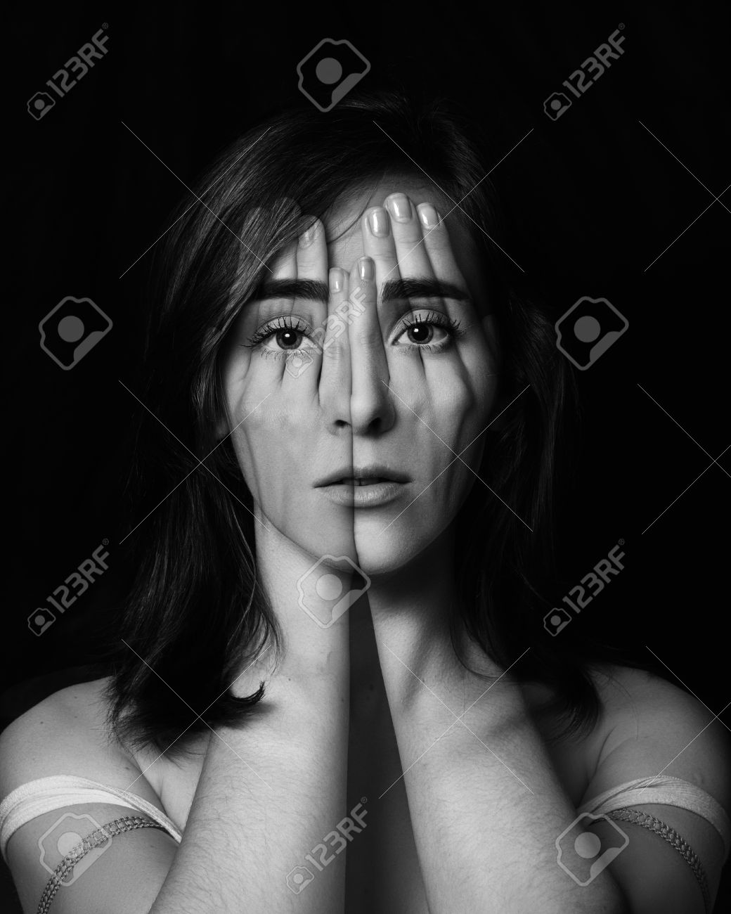 Surreal portrait of a young girl covering her face and eyes stock stock photo surreal portrait of a young girl covering her face and eyes with her handsuble exposure black and white publicscrutiny Gallery