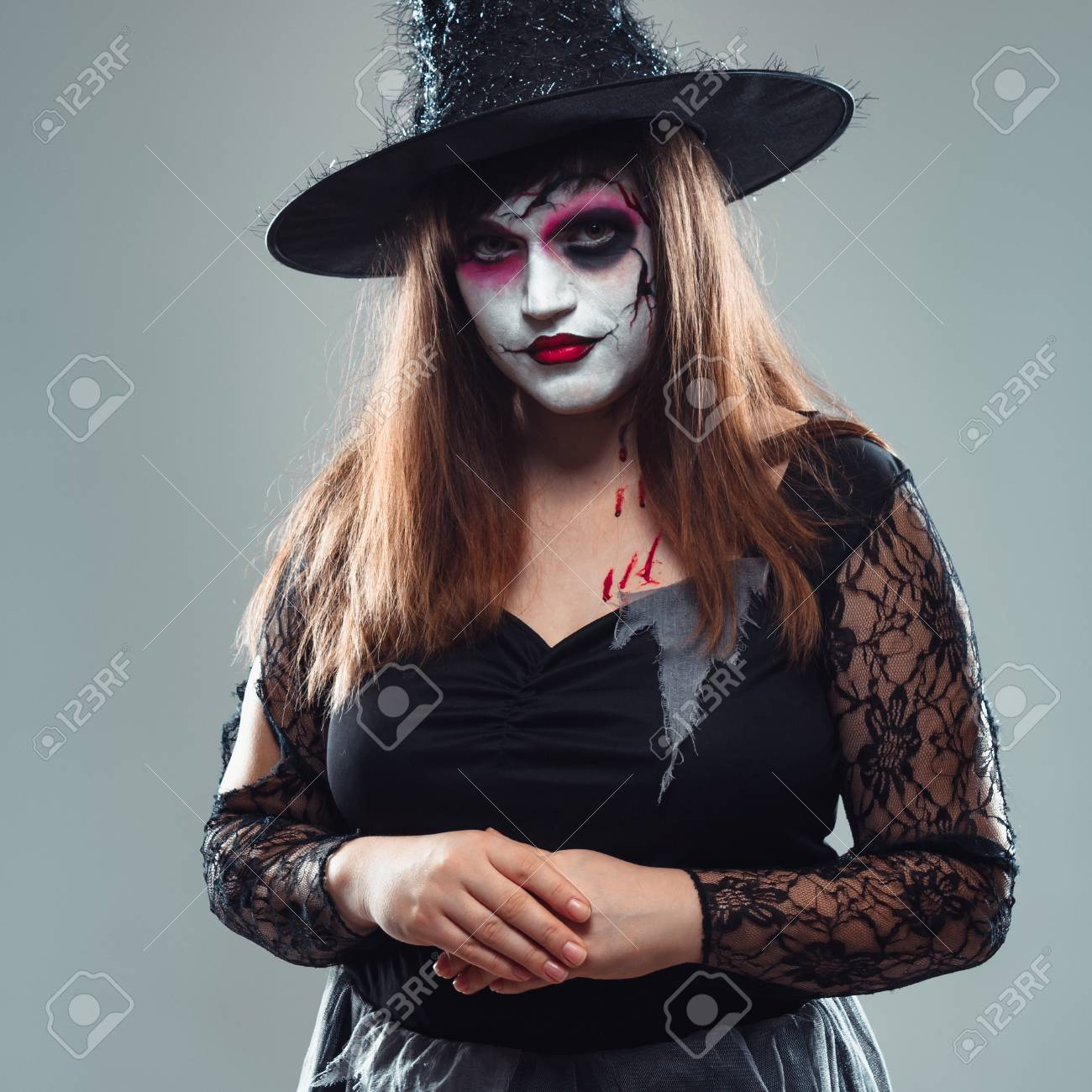 Gothic Young Woman In Witch Halloween Costume With Hat Standing Over