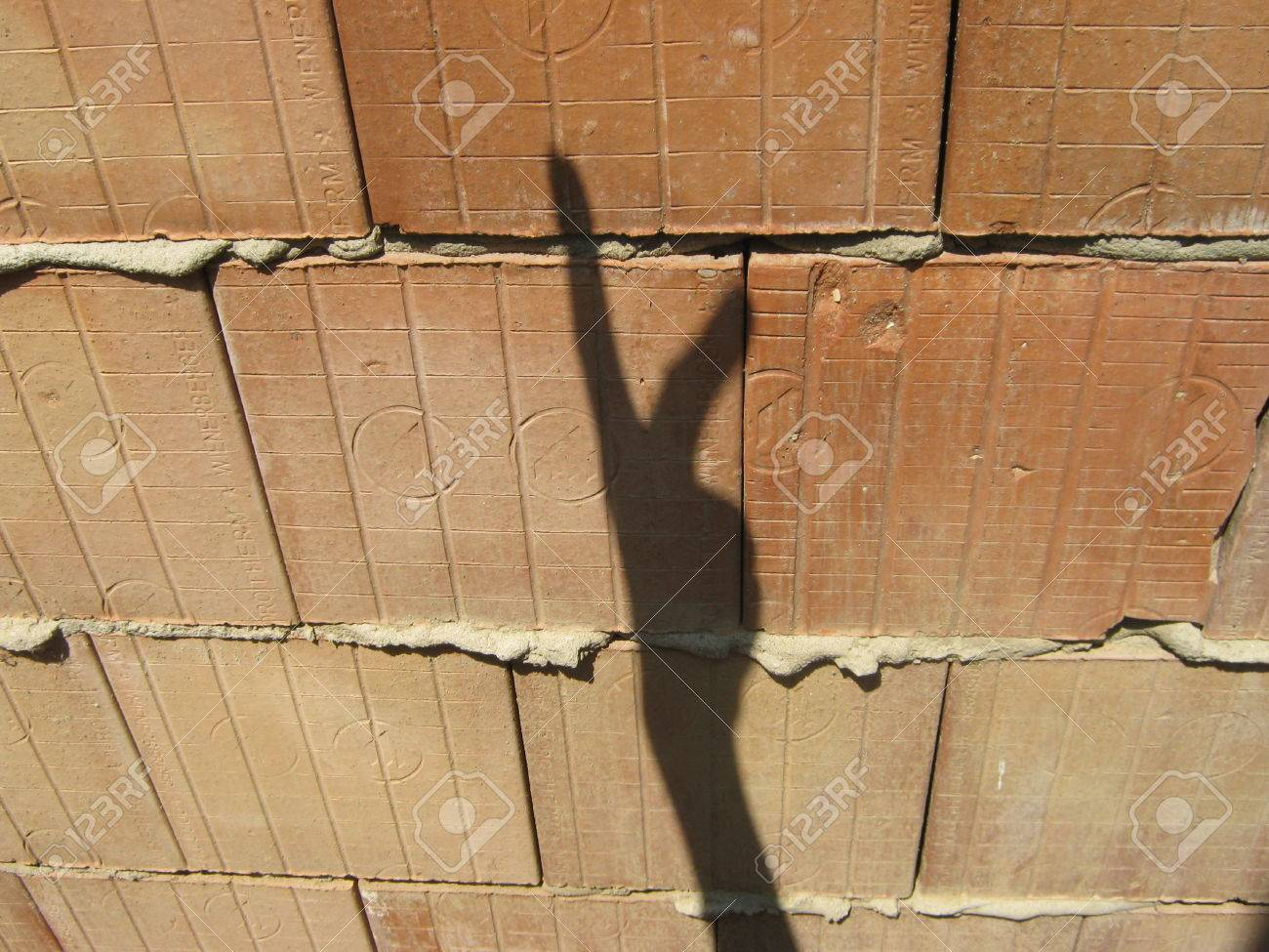 Shadow hand makes signs on unplastered porous brick wall Stock Photo - 25028478
