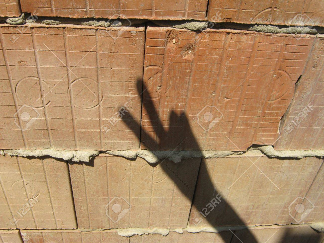 Shadow hand makes signs on unplastered porous brick wall Stock Photo - 25028481
